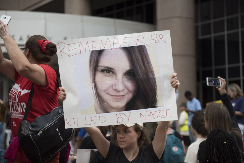 "Image of a woman in a black shirt holding aloft a large photo portrait of Heather Heyer with the words ""Remember Her"" above and ""Killed By Nazi"" below the photo. To her left is another woman in a red ""Dump Trump"" shirt."