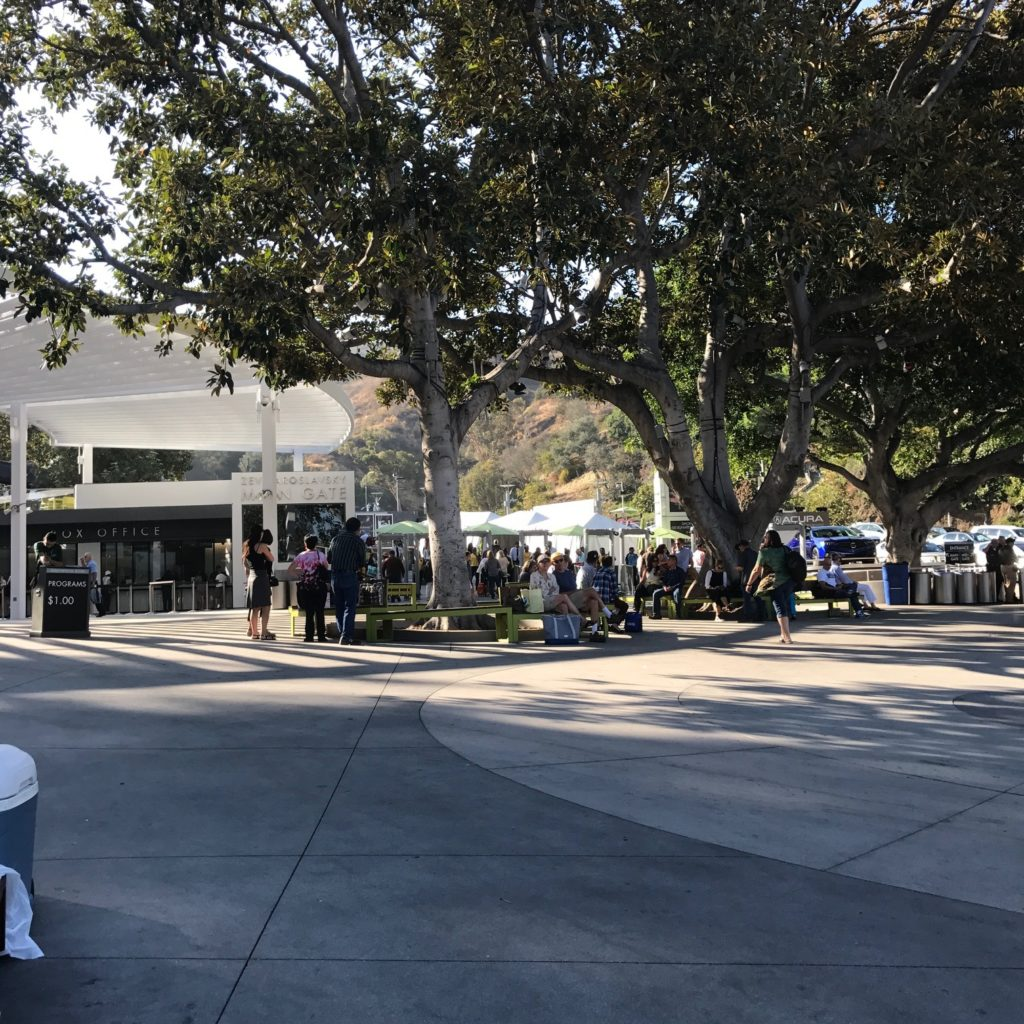 Image of the Hollywood Bowl entrance grounds with people standing under shade trees and the box office in the background.