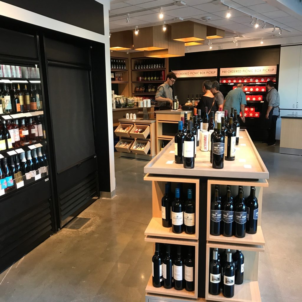 Image of the Hollywood Bowl Marketplace with open-shelf wine cooler to the left and display of wine bottles in the foreground. In the background an employee is checking out some shop patrons while another employee assists a man in the pre-order pickup area.