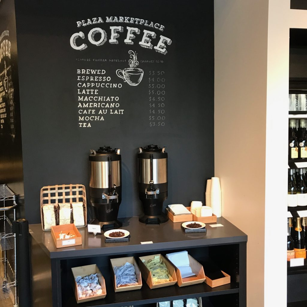 Image of the Plaza Marketplace coffee menu above a shelves containing coffee urns, cups, and fixings.