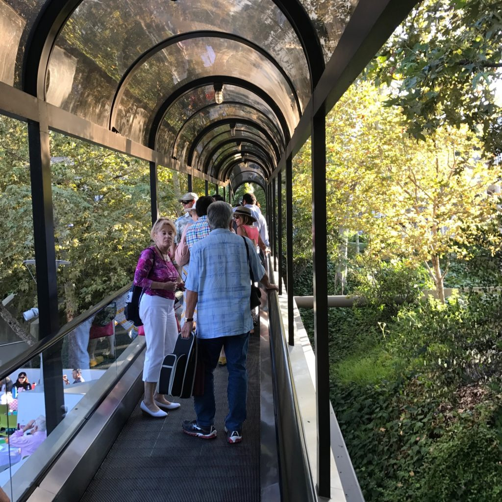 Image is of the Hollywood Bowl escalator, which is flat and operates as a moving walkway. It has a clear canopy over top and several concertgoers are standing in conversation as they ride.
