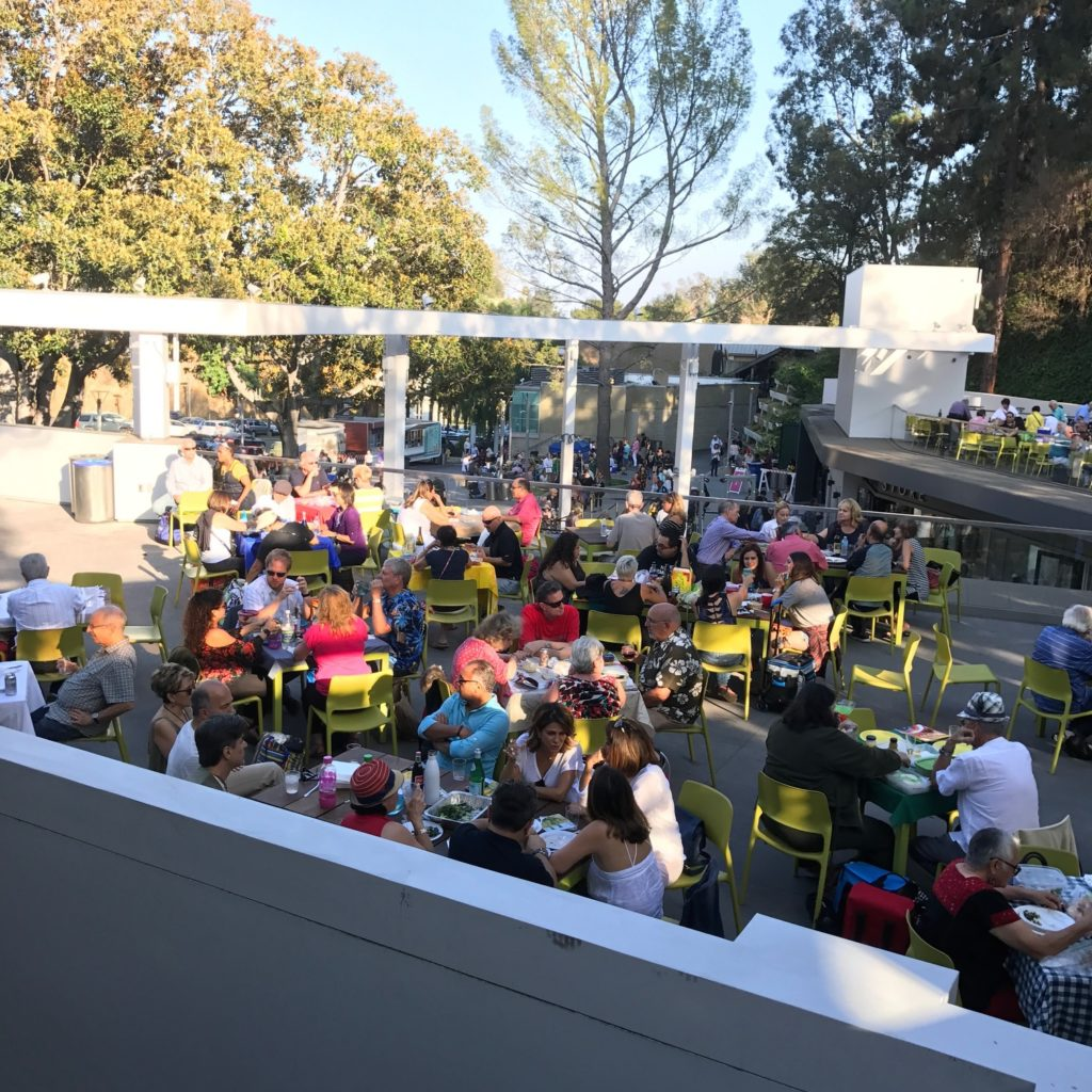 Image of the picnic area at the Hollywood Bowl with concertgoers seated in chartreuse-colored chairs around small tables in dappled golden sunlight.