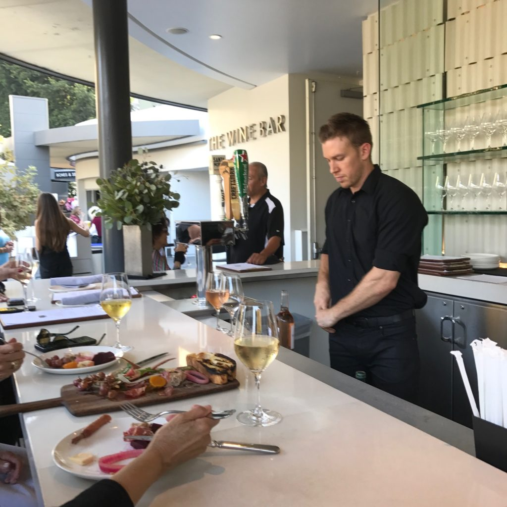 Image of a bartender behind the counter at the Hollywood Bowl Wine Bar. On the bar is a wood board featuring a selection of charcuterie, two glasses of chilled white wine, and the filled plates of two diners.