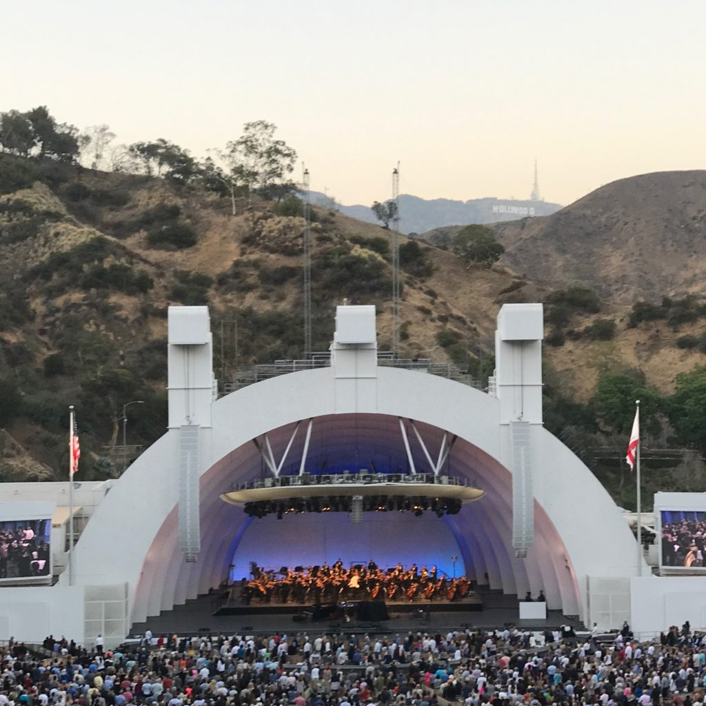 Image of the Hollywood Bowl acoustic concert shell at dusk with the hills and Hollywood sign in the background.