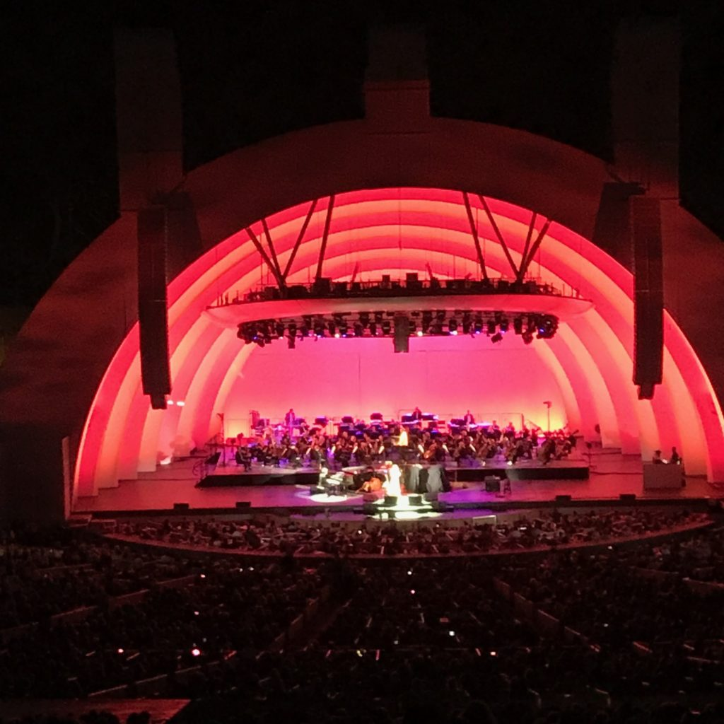 Image is of several performers downstage in the center of the Hollywood Bowl shell with the orchestra seated upstage. The shell is lit with vibrant orangy-red and fuschia lights.