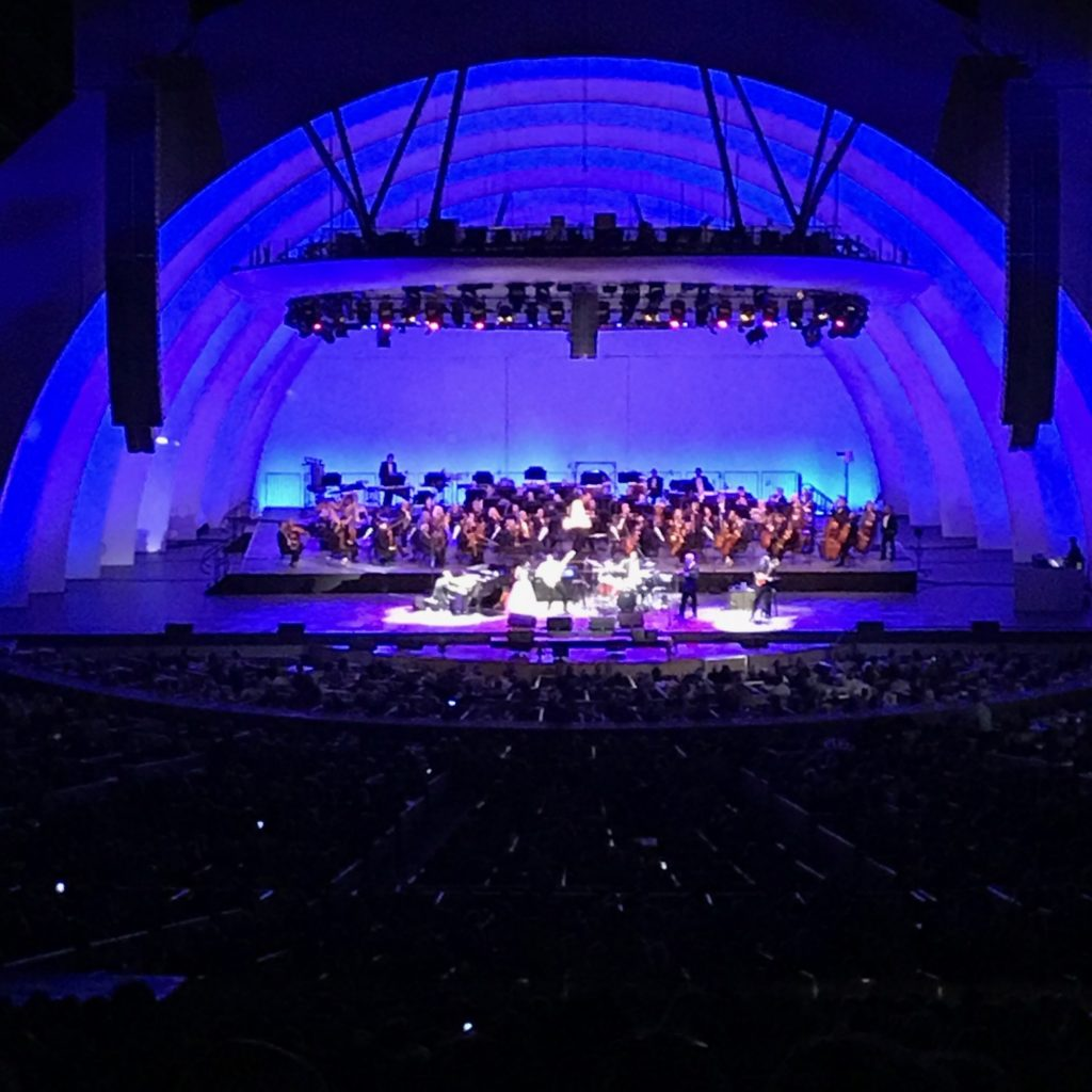 Image is of several performers downstage in the center of the Hollywood Bowl shell with the orchestra seated upstage. The shell is lit with deep blue light and white spotlights on the performers.